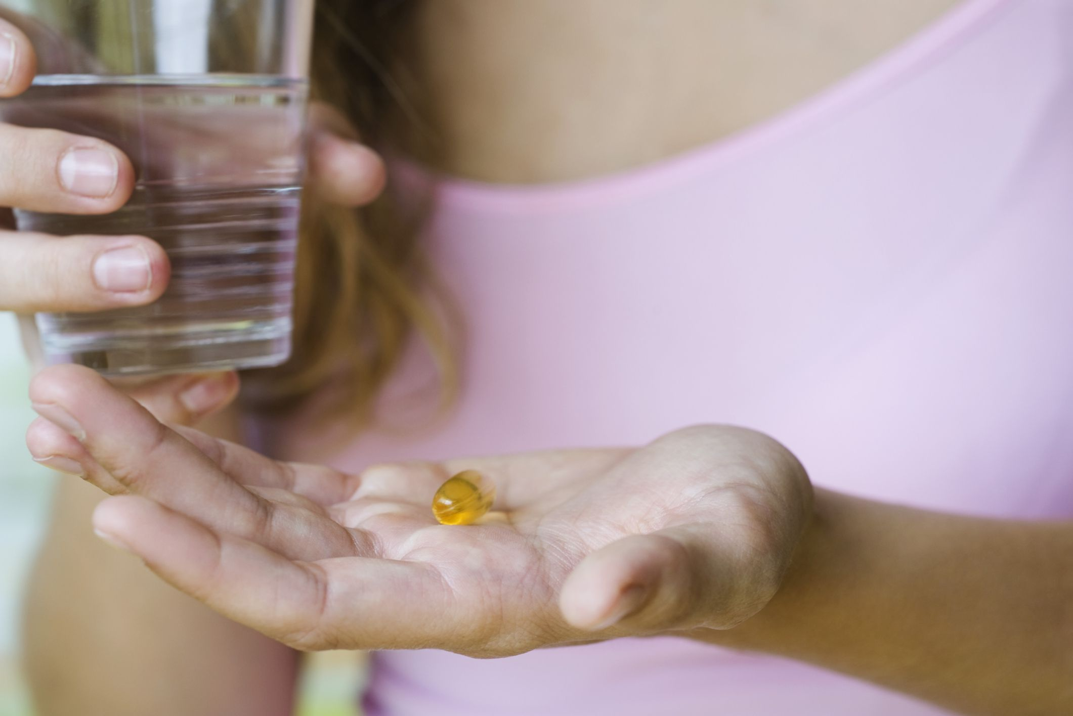 Woman holding fish oil supplement and water