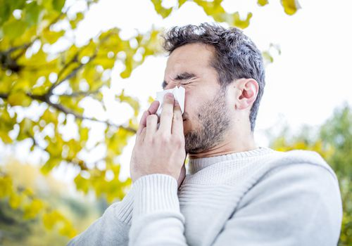 A man sneezing into a tissue