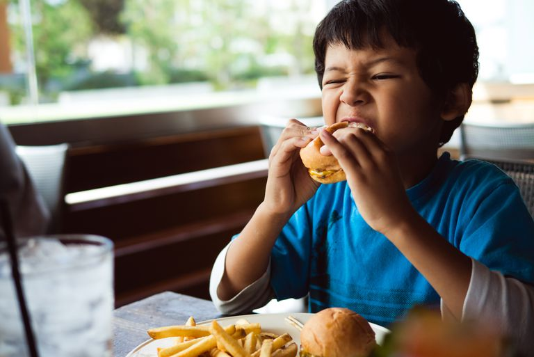 Boy eating cheeseburger