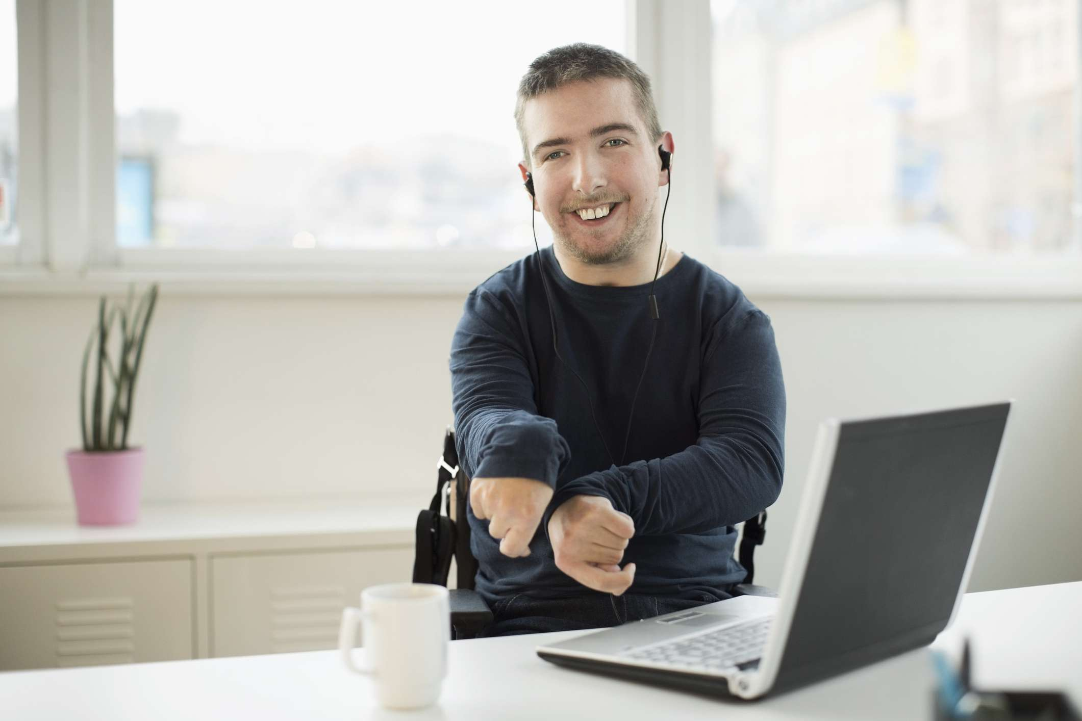 Portrait of happy disabled businessman with laptop at desk in office - stock photo