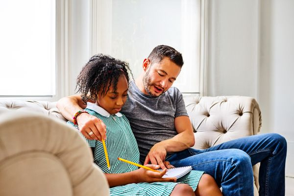 Transgender father and daughter on couch doing homework