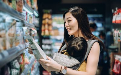 Young Asian mother grocery shopping with little daughter and choosing for organic baby food in the supermarket - stock photo