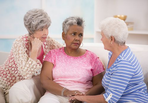 Sad senior woman being comforted by two friends