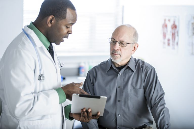 Older male patient talking with doctor over a tablet