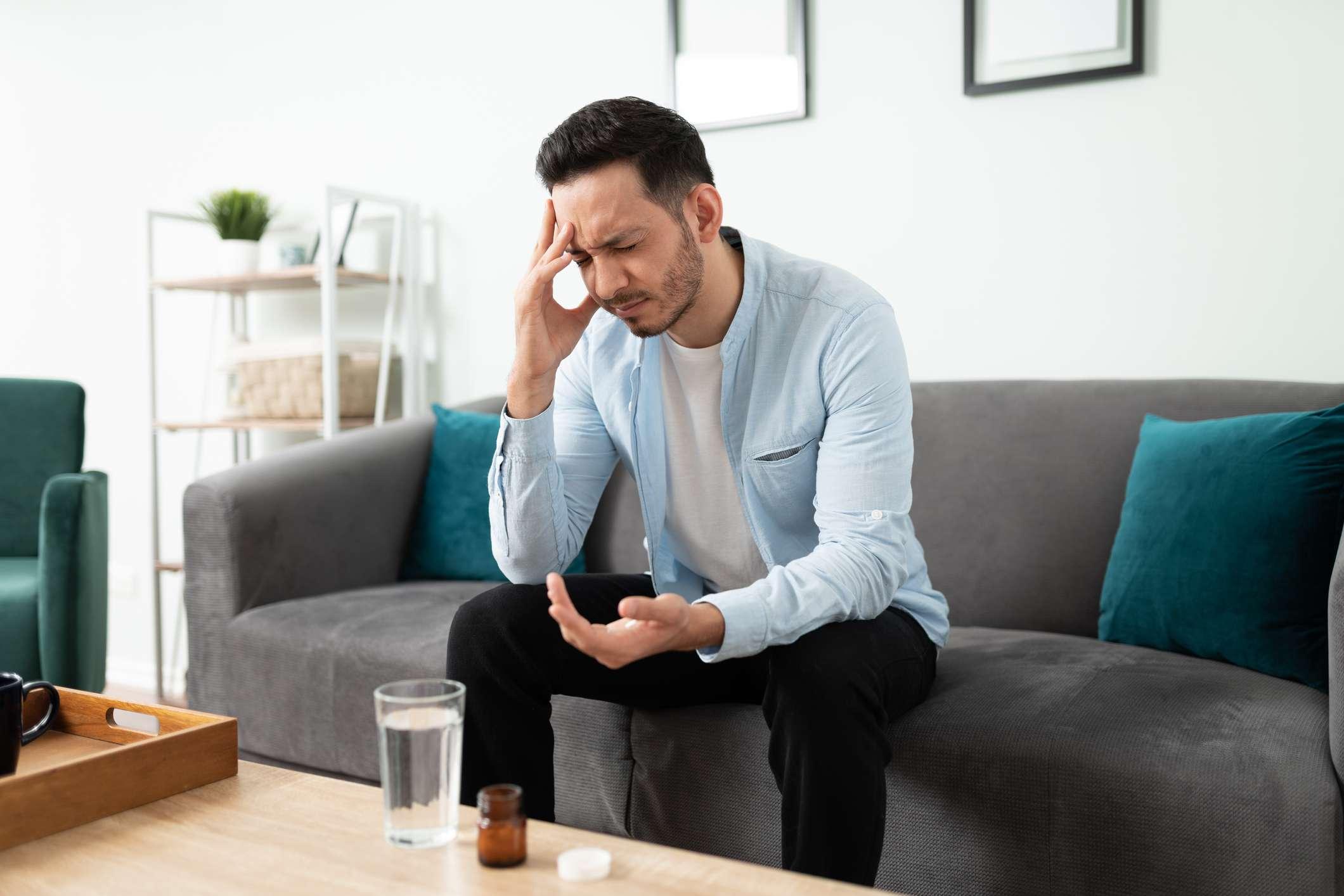 Young man taking pills for a headache