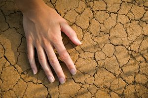 Female hand touching dry red soil