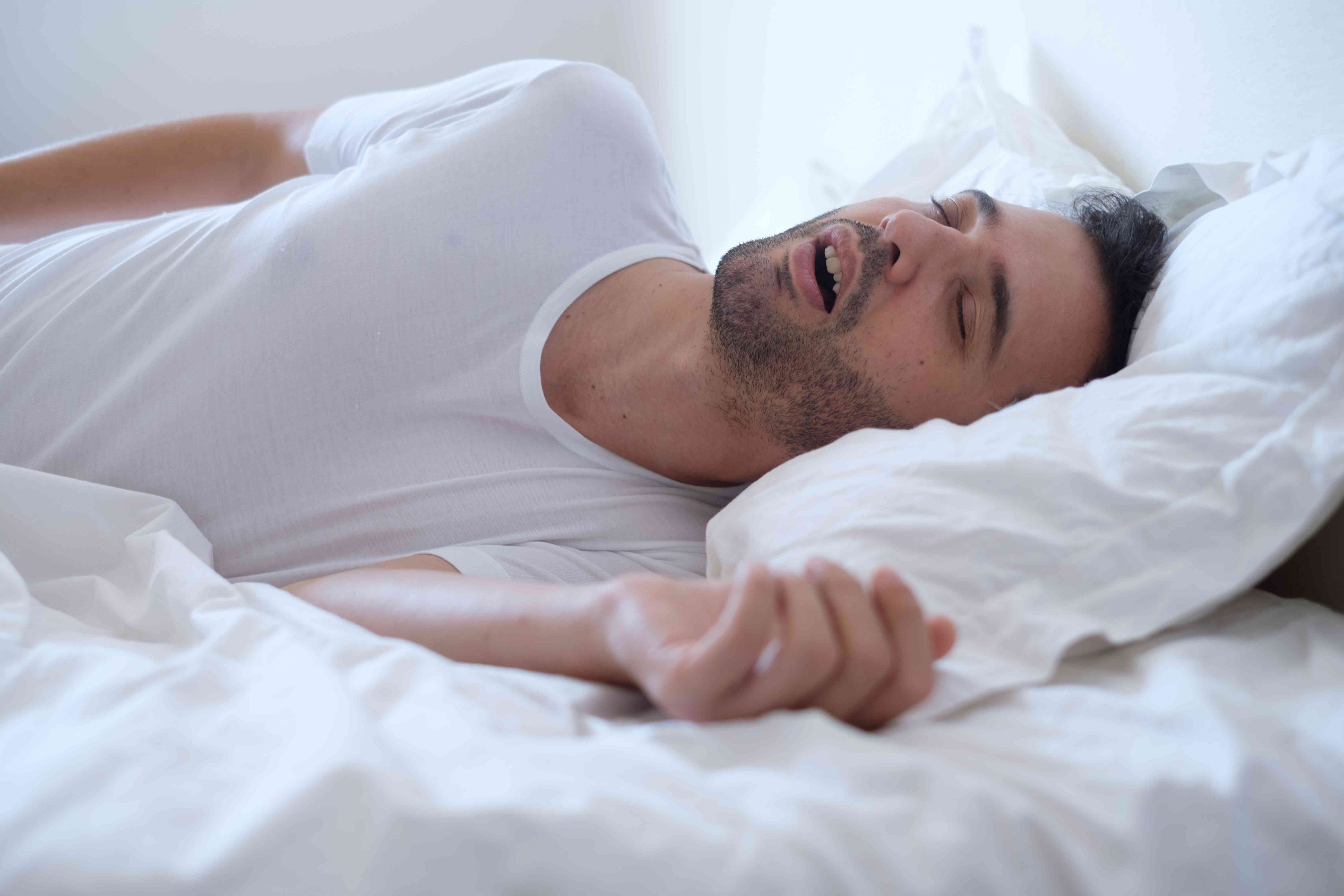 A man snoring while he sleeps in bed