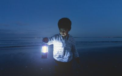 Boy in a long-sleeved jacket on the beach at night holding a lamp.