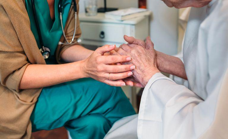Nurse Consoling Senior Patient In Hospital