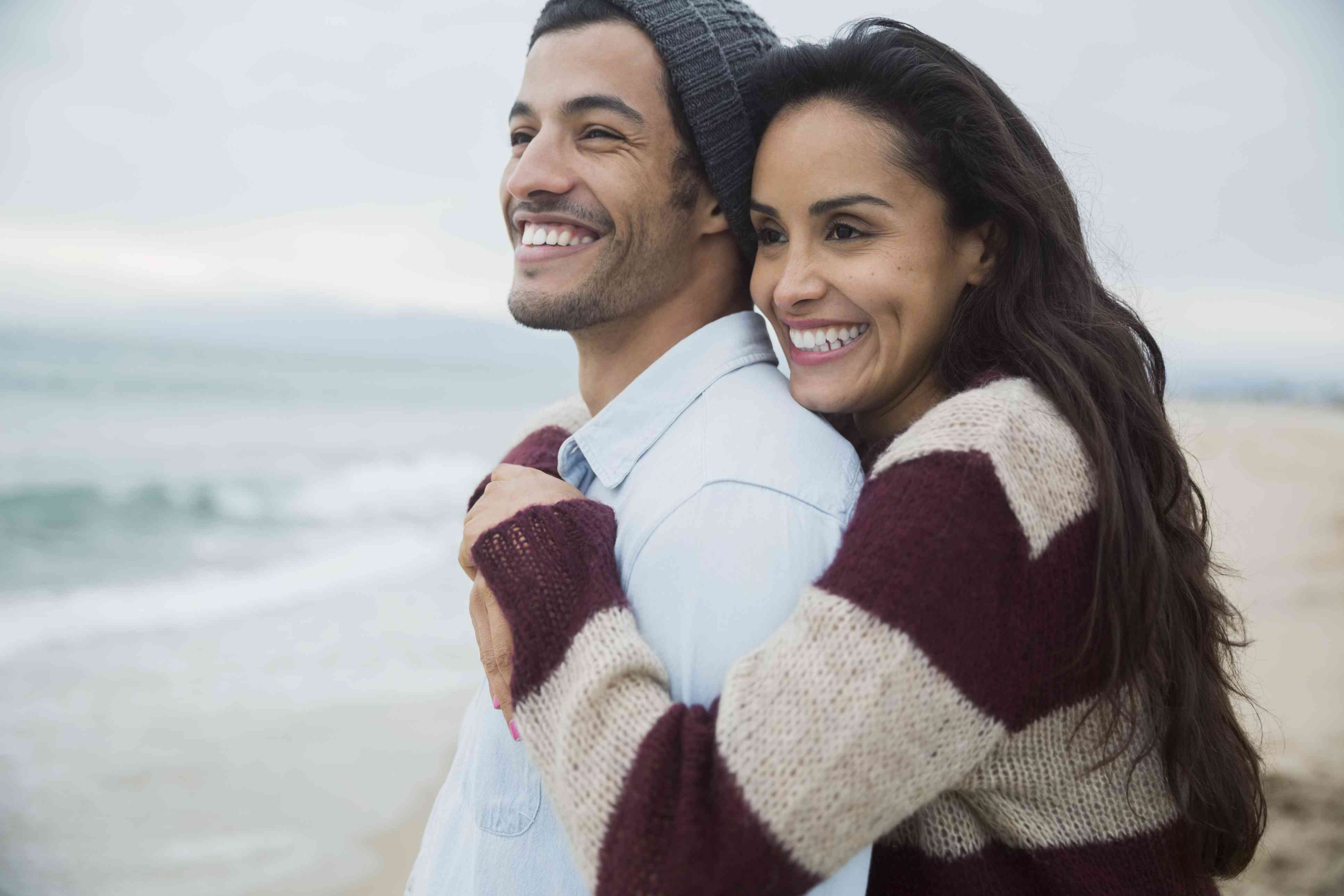 A man and a woman hugging on the beach