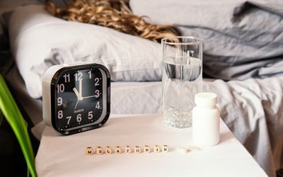 curly haired woman laying in bed with melatonin and water on night stand.