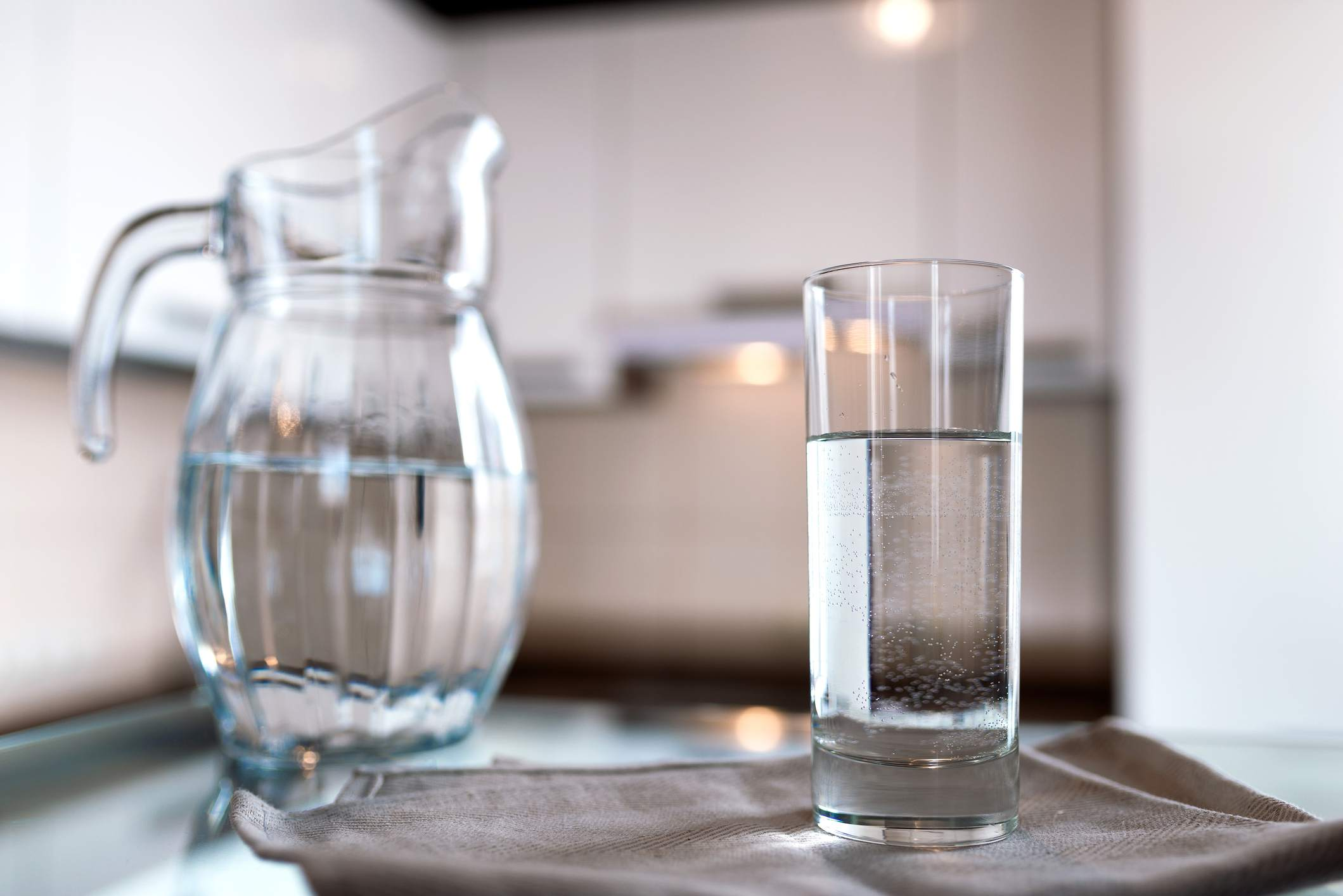 A glass of fresh water with crafin on the background of a modern kitchen.