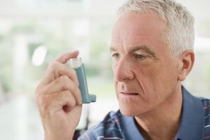 Senior man about to use an inhaler