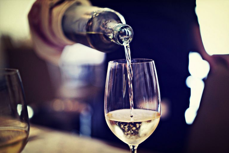 Restaurant server pouring white wine