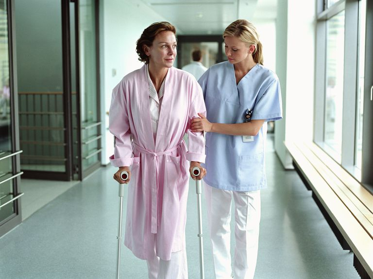 nurse helping woman walk with sticks in hospital