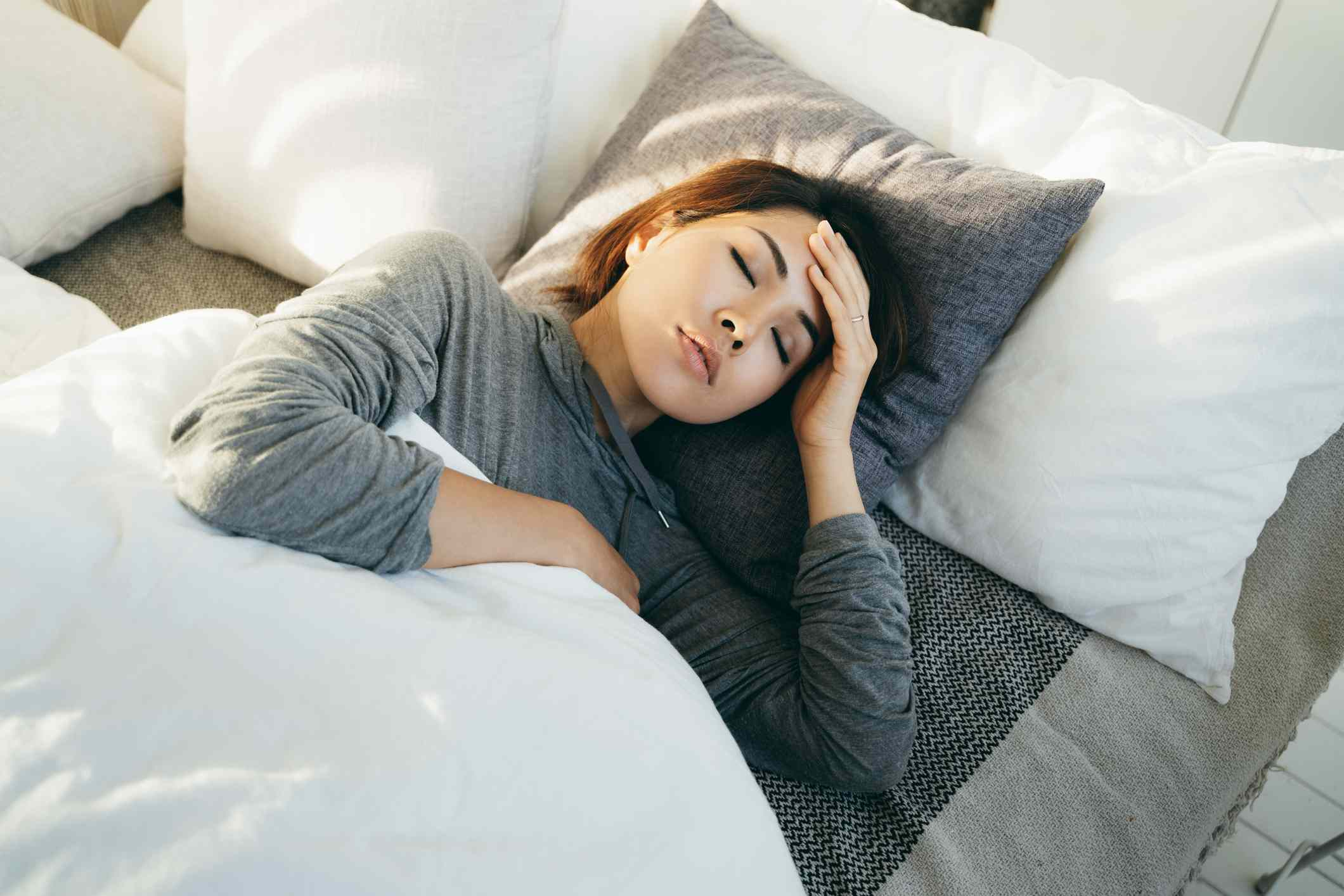 Young Asian woman with hand on forehead lying in bed and feeling sick
