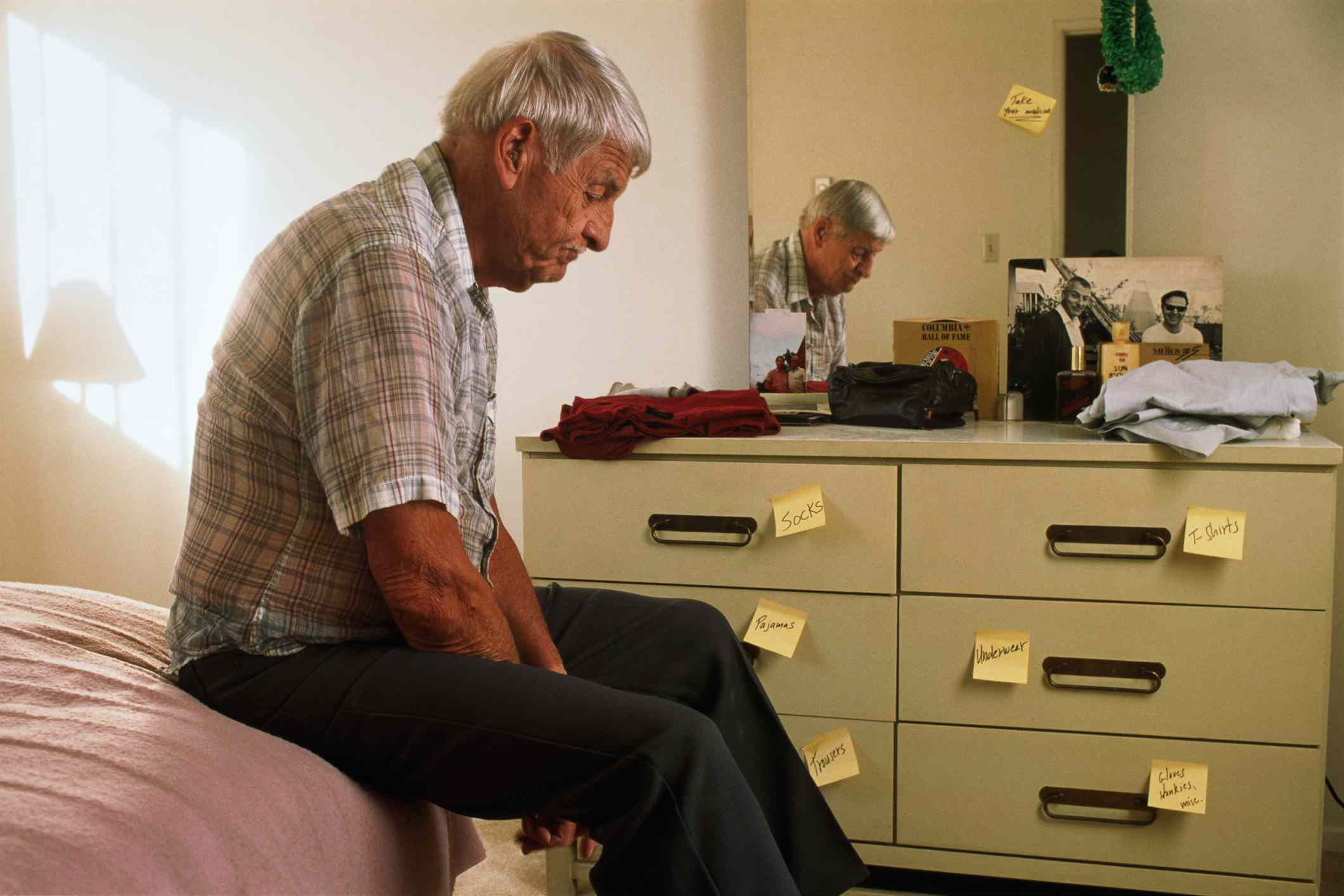 Male Alzheimer's patient sitting on bed, reminders on dresser drawers