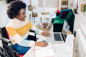 Young black woman in a wheelchair working from home on a laptop at a desk