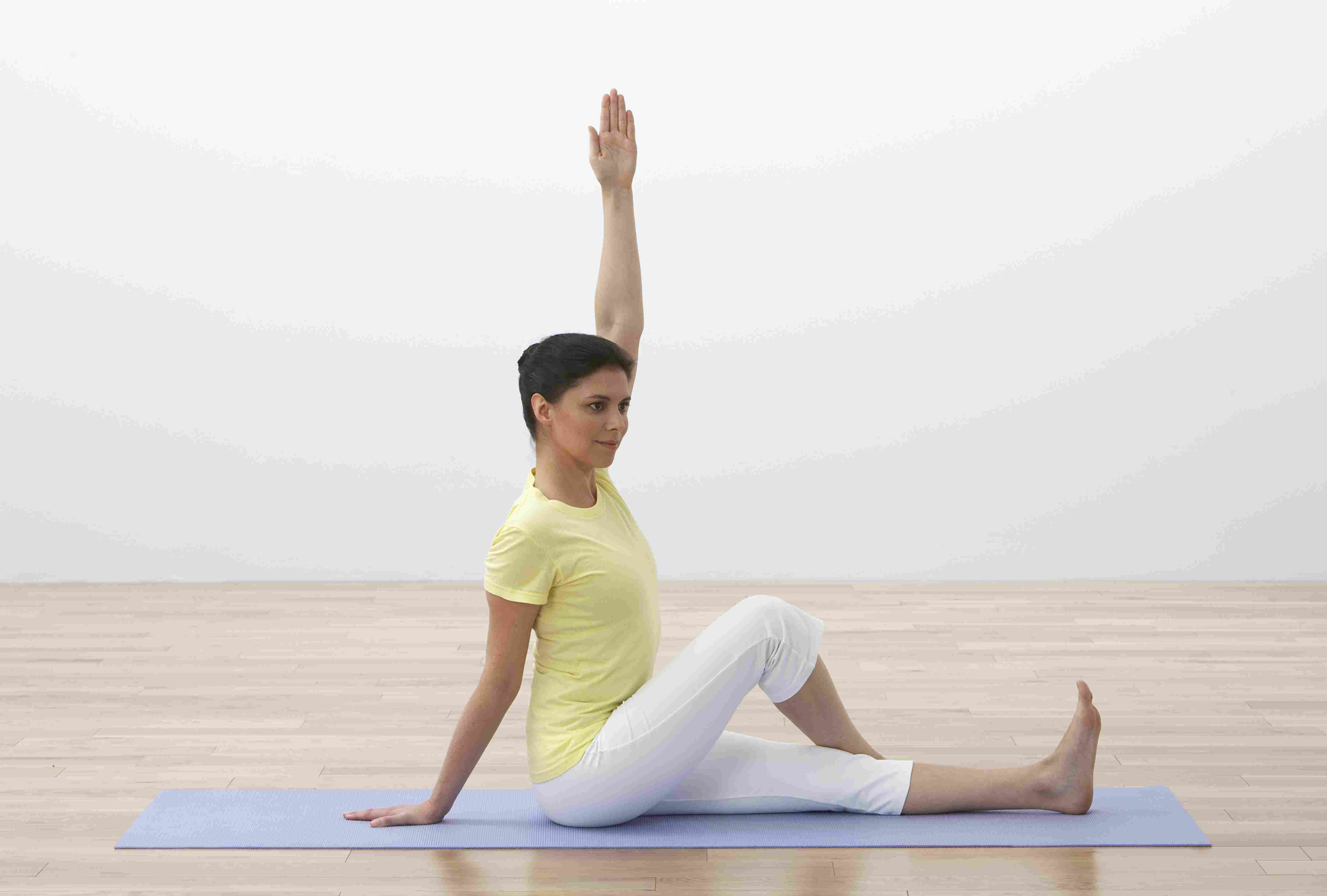 Woman on yoga mat performing spinal twist yoga exercise