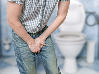 Young man in bathroom with groin pain
