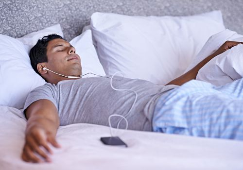 Man relaxing before bedtime by listening to music to feel sleepy