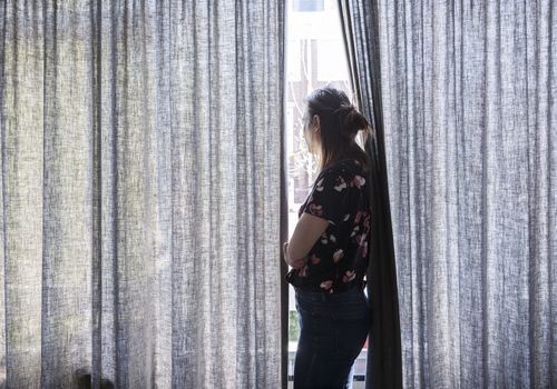 Woman staring out a window during quarantine.