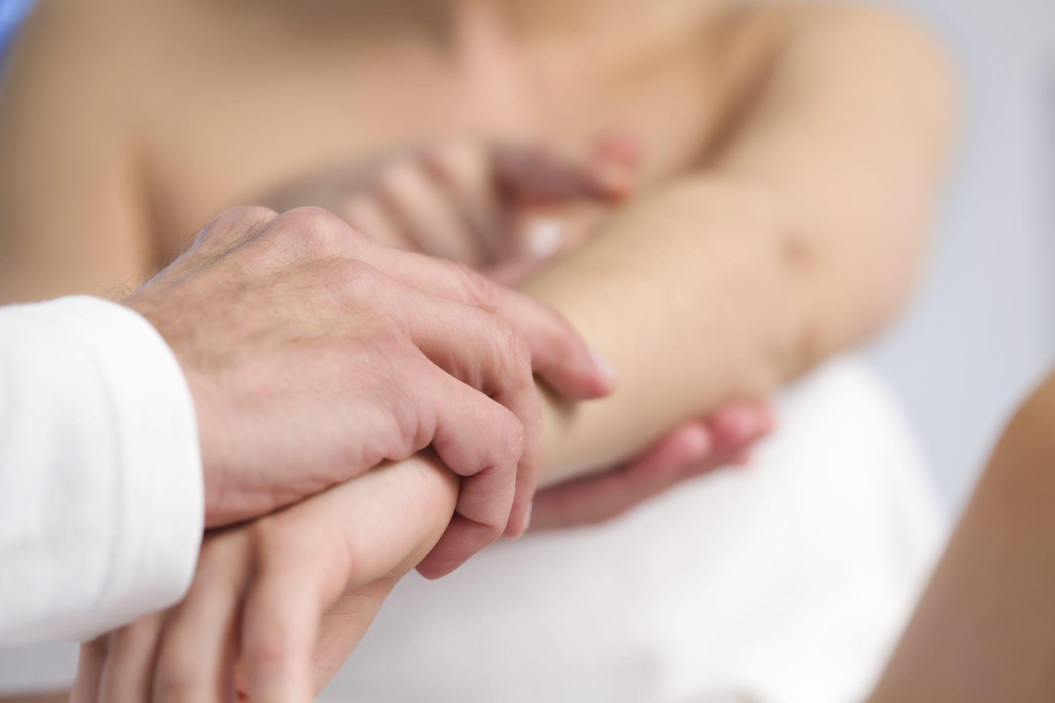 doctor examining arm of patient