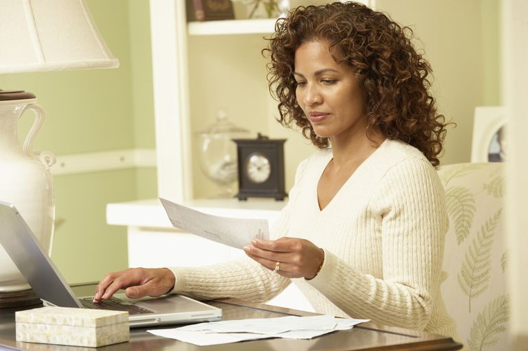 Woman sitting in front of laptop, paying bills online