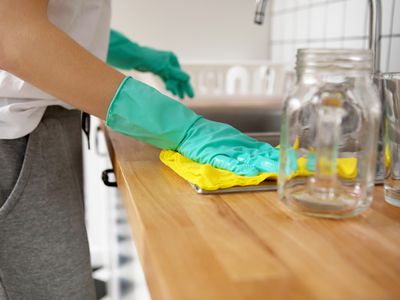 cleaning kitchen counter wearing gloves