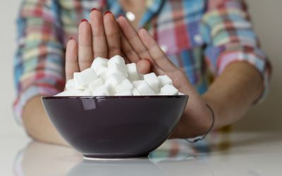 Woman refuses a bowl filled with sugar cubes