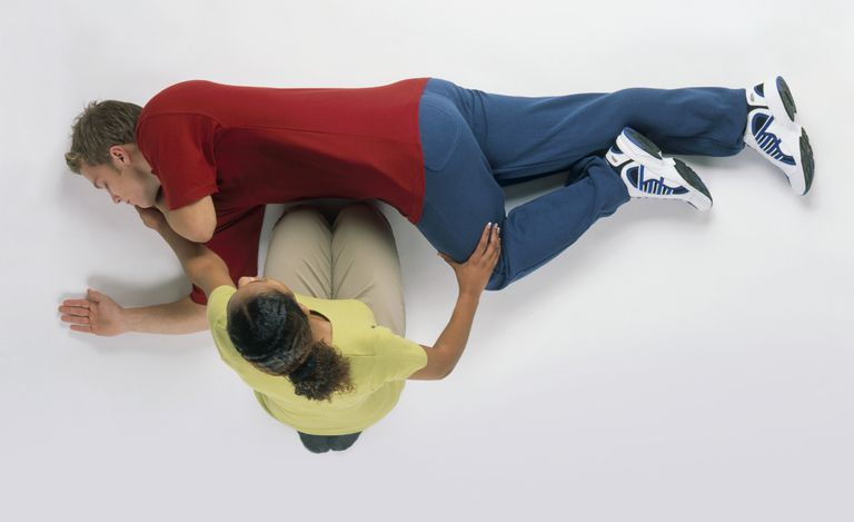 woman putting man into recovery position