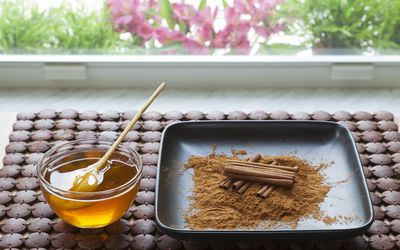 A bowl of honey and cinnamon sticks on a tray