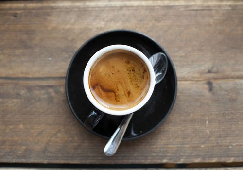 Freshly brewed espresso in a cup on a wooden table, overhead shot