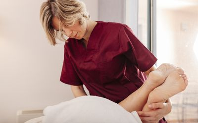 physical therapist stretching a person's legs