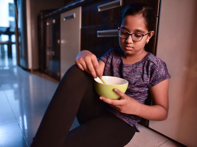 Young girl eating from bowl while sitting on kitchen floor