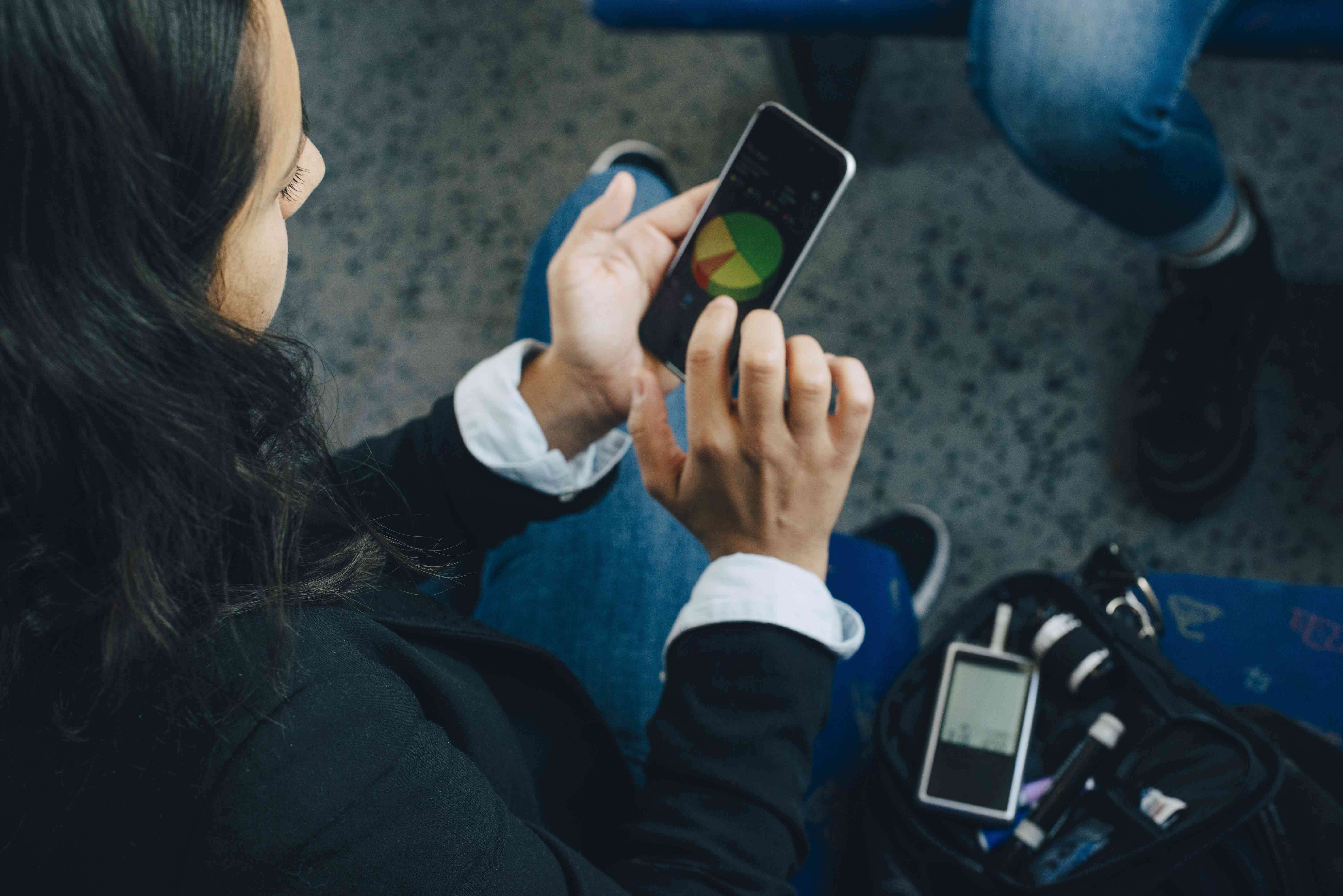 Woman checking blood sugar level and using mobile phone in train