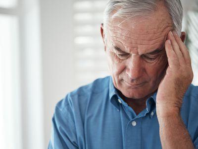 Senior man holding his head