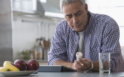 Hispanic man examining prescription bottle in kitchen - stock photo