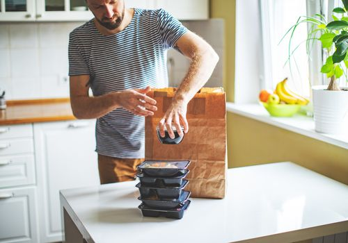 A young white man taking take out food containers out of a brown paper bag in the kitchen.