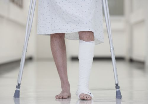 Man in a hospital gown with a bandaged leg using crutches