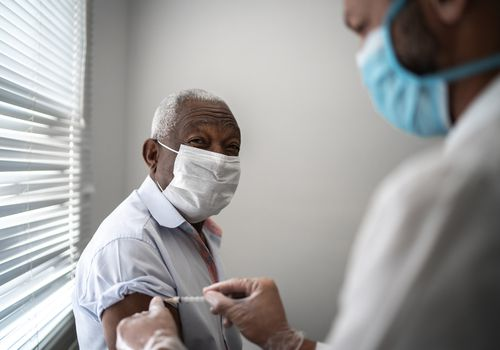 Black older man receiving a vaccine shot.
