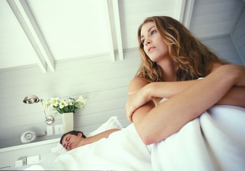 Woman sitting in bed awake while man sleeps next to her