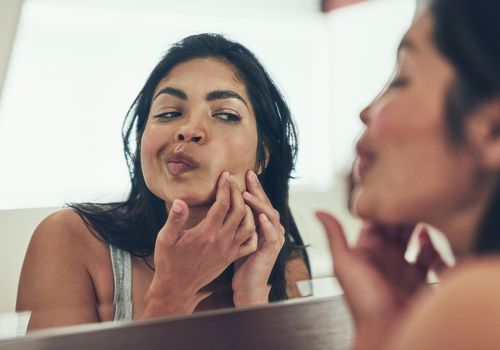 woman looking at pimple in mirror