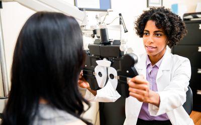 Annual eye exam by the optometrist - stock photo