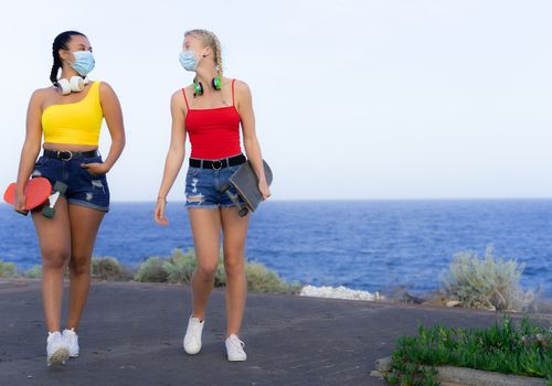 Two young women walking together by the ocean in the summer, holding skateboards and wearing face masks.