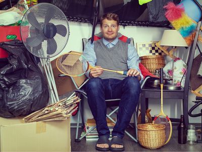 A man holding a badminton racket sits on a chair surrounded by clutter.