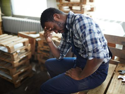 Exhausted employee in sits in a warehouse in pain