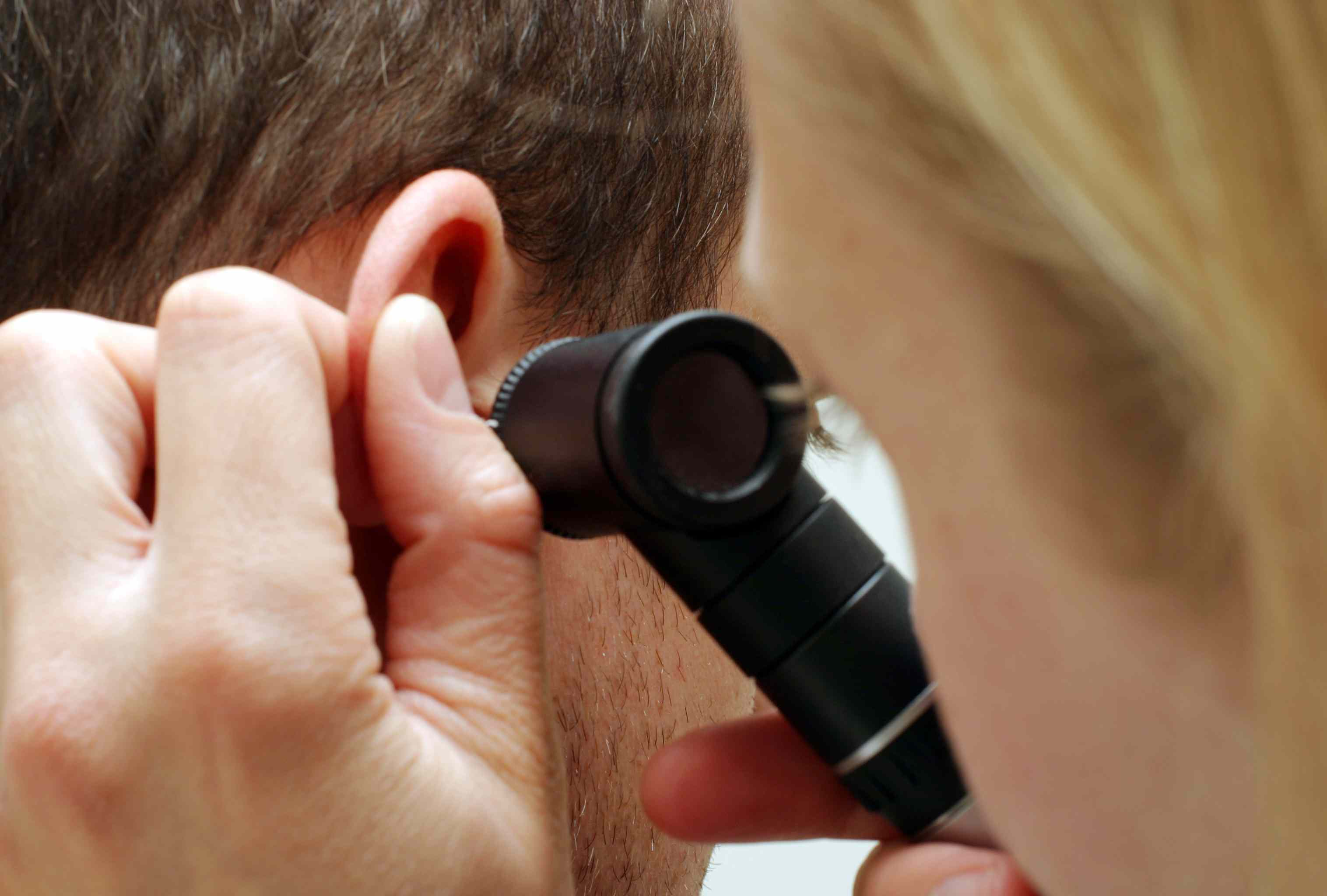 Doctor examining the ear of a patient