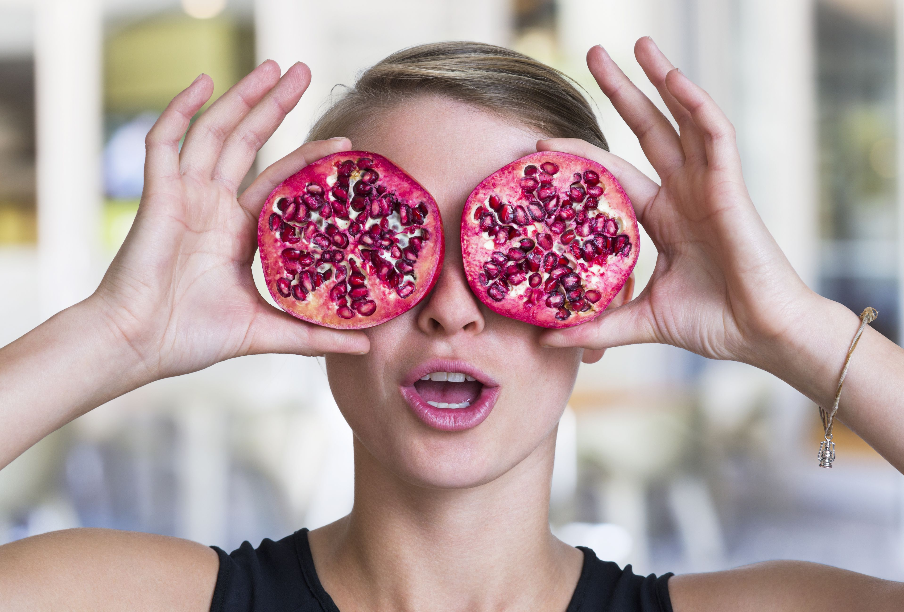 Woman holding two pomegranate halves up to her eyes