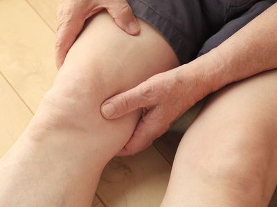Midsection of Man Holding Thigh While Sitting On Hardwood Floor